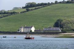 在与草甸的Youghal海湾停泊的小船爱尔兰在背景中 免版税库存图片