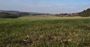 在与蓝天和云彩的秋天天期间有小小山的草甸在普劳恩市附近的背景在Vogtland 免版税库存图片