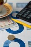 在与蓝色圆形统计图表的纸板料安置的欧洲硬币 免版税库存图片