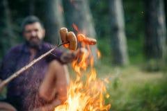 在与被弄脏的人的篝火烤的香肠自然本底的 库存照片