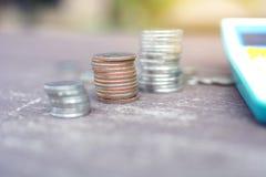 在与被弄脏的庭院的老木桌安置的三堆泰国硬币和计算器 免版税库存照片
