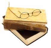在与被撕毁的捆绑和一块残破的脊椎的一本旧书是glasse 图库摄影