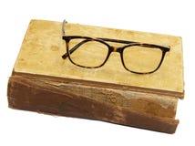 在与被撕毁的捆绑和一块残破的脊椎的一本旧书是glasse 库存图片