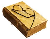 在与被撕毁的捆绑和一块残破的脊椎的一本旧书是glasse 免版税库存照片
