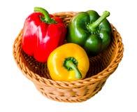 在与裁减路线的白色背景隔绝的篮子的红色,绿色和黄色甜椒胡椒 免版税库存图片