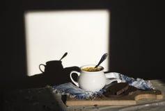 在与装饰品样式的桌蓝色餐巾和盛汤盖碗用在太阳面包木板种子黑暗背景的黄色汤 图库摄影
