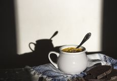 在与装饰品样式的桌蓝色餐巾和盛汤盖碗用在太阳面包木板黑暗背景的黄色汤 库存照片