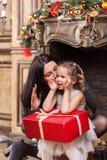 在与装饰的一个壁炉附近照顾亲吻她有圣诞节礼物的逗人喜爱的小女孩 免版税库存照片