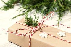 在与装饰的牛皮纸或当前箱子包裹的圣诞节礼物在土气木背景 定调子 免版税库存图片