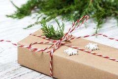 在与装饰的牛皮纸或当前箱子包裹的圣诞节礼物在土气木背景 库存图片