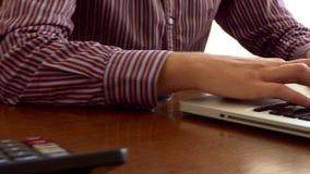 在与计算器的表安置的一台白色膝上型计算机的男性手工 股票录像