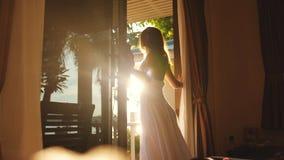 在与透镜火光作用的日出期间深色的女孩打开门在清早 库存图片