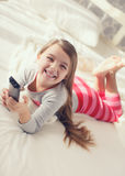 在与遥控电视的床上的小女孩 图库摄影