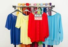 在与销售的挂衣架显示的逗人喜爱的红色,黄色,蓝色女衬衫签字 库存照片