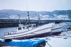 在与雪秋天的海滩靠码头的日本白色渔船在wi 库存图片