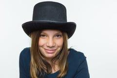 在与高顶丝质礼帽的黑色打扮的女孩 免版税图库摄影