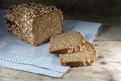 在与整个五谷的在土气木头,黑暗的backgr的大面包和种子上添面包 库存照片