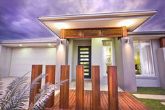 在与紫色天空的晚上被照亮的现代豪宅 免版税库存照片