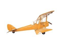 在与cli的白色背景隔绝的减速火箭的样式黄色双翼飞机 免版税图库摄影