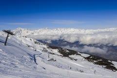 在与Mt的冬天期间在Pila意大利滑雪区域的驾空滑车在积雪的阿尔卑斯和杉树的 Blanc在法国可看见在ba 库存图片