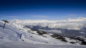在与Mt的冬天期间在Pila意大利滑雪区域的驾空滑车在积雪的阿尔卑斯和杉树的 Blanc在法国可看见在ba 免版税库存图片