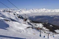在与Mt的冬天期间在Pila意大利滑雪区域的驾空滑车在积雪的阿尔卑斯和杉树的 Blanc在法国可看见在ba 免版税库存照片