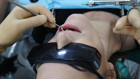 在专业实践内阁 牙医审查耐心关闭  医生拿着牙齿工具-镜子 女性患者 影视素材