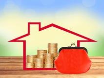 在专栏在房子里和红色钱包的许多硬币在木桌上 免版税库存图片