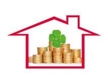 在专栏的许多硬币在房子和三叶草里生叶 库存照片