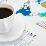 在世界地图和一些市场图-接近的射击的咖啡杯 免版税库存图片