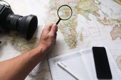 在世界地图的愉快的年轻行家夫妇计划旅行 顶视图 库存图片
