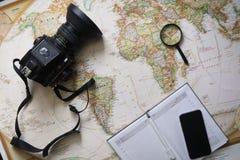 在世界地图的愉快的年轻行家夫妇计划旅行 顶视图 库存照片