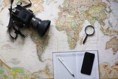 在世界地图的愉快的年轻行家夫妇计划旅行 顶视图 免版税图库摄影