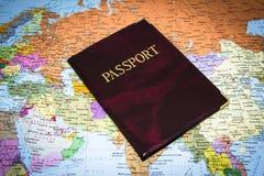 在世界地图的护照 图库摄影