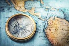 在世界地图的磁性指南针 旅行,地理,航海, tou 免版税库存照片