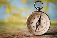 在世界地图的磁性指南针 库存图片