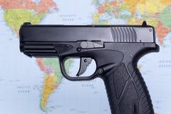 在世界地图背景的黑枪 库存图片