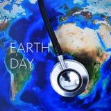 在世界地图(装备由美国航空航天局)和文本eart的听诊器 免版税库存照片