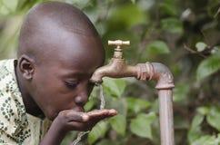在世界标志的水scarsity 非洲男孩乞求为wate 免版税图库摄影