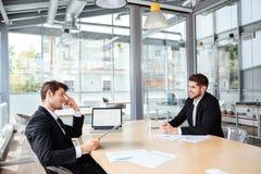 在业务会议的两个愉快的年轻商人 免版税库存照片