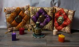 在东方样式陶瓷茶壶和色的b的五颜六色的坐垫 免版税库存图片