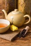 在东方茶具旁边的郁金香绽放在黄麻布料 库存图片