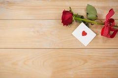 在丝带和心脏包裹的红色玫瑰打印了信封 免版税库存图片
