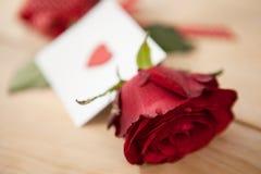 在丝带和心脏包裹的红色玫瑰打印了信封 图库摄影