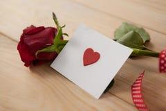 在丝带和心脏包裹的红色玫瑰打印了信封 库存照片