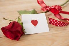 在丝带和心脏包裹的红色玫瑰打印了信封 免版税库存照片