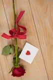 在丝带和心脏包裹的红色玫瑰打印了信封 库存图片