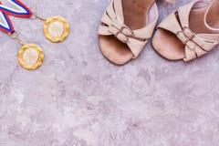 在丝带的两枚体育交谊舞的奖牌和鞋子 免版税图库摄影