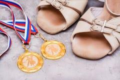 在丝带的两枚体育交谊舞的奖牌和鞋子 免版税库存照片
