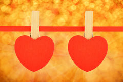 在丝带的两红色心脏在金黄闪烁迷离 免版税库存照片